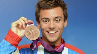 Tom Daley holding up his bronze medal.