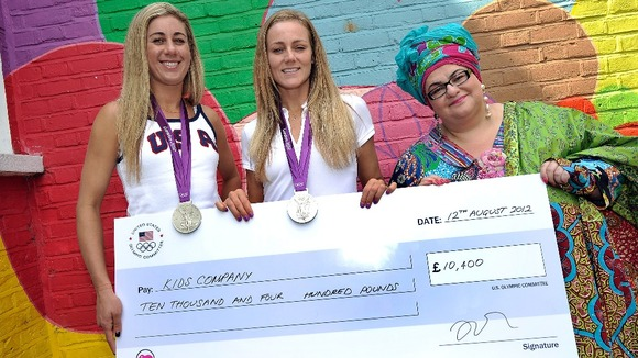 April Ross and Jen Kessy present a check to Kid's Company founder Camila Batmanghelidjh
