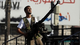 A Free Syrian Army fighter holds an anti-aircraft gun as he looks for a Syrian Air force helicopter in Aleppo