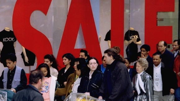 Shoppers make their way past a large sale sign in a shop window on Oxford Street.
