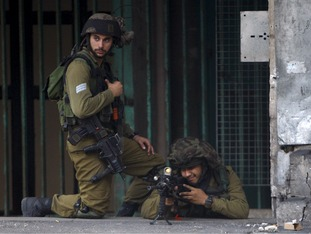 An Israeli soldier aims his weapon at Palestinians during clashes on Friday.