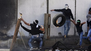Palestinians clash with Israeli border police during clashes at a checkpoint between a refugee camp and Jerusalem.