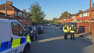 The road in Salford is cordoned off after the shooting of a mother and son