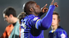 Adebayo Akinfenwa celebrates scoring for AFC Wimbledon.