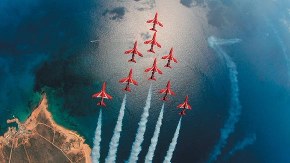 The Red Arrows fly over the sea
