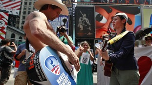 Times Square entertainer Naked Cowboy plays guitar with protester demonstrating in solidarity with Russian punk band Pussy Riot in New York