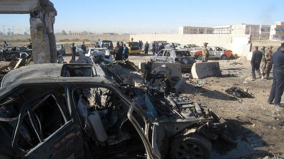 People and security forces inspect the scene of a car bomb attack in Kirkuk