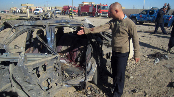 A man gestures at a destroyed vehicle at the scene of a car bomb attack in Kirkuk, Iraq