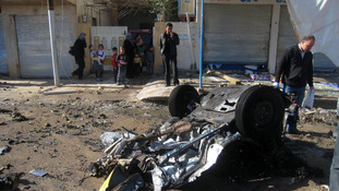 People inspect the scene of a car bomb attack in Kirkuk, Iraq