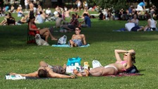People enjoy the hot weather on Clapham Common in London.