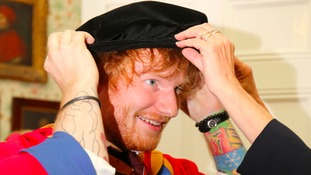 Ed Sheeran tries on his robes before receiving an honorary degree from University Campus Suffolk in Ipswich.
