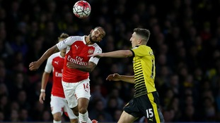 Theo Walcott battles for the ball with Watford'?s Craig Cathcart (right)