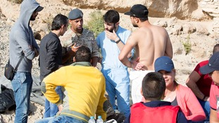 An RAF servicemen talks to people on the beach.