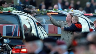 A mourner places a flower on one of the hearses carrying the bodies of six soldiers as they pass through Carterton in Oxfordshire