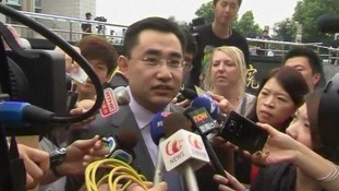 He Zhengsheng, the lawyer for the family of Neil Heywood, is surrounded by reporters as he leaves court in China