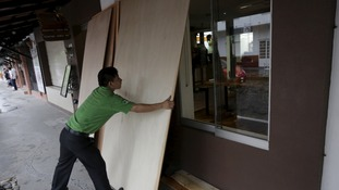 Employee boards up a shop window