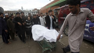 A man wheels a body of a woman, who died in an earthquake, at the Lady Reading hospital, Peshawar