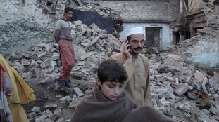 Residents walk past the rubble of a house after it was damaged by an earthquake in Mingora, Swat, Pakistan,