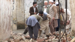 Residents gather to clear a path by removing rubble from a house after it was damaged by an earthquake in Mingora,
