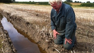 Farmer Brian Sutton inspects the flooding in his fields in Leicester