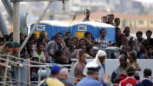 Migrants and refugees disembark from HMS Enterprise in Catania, Italy, in October.