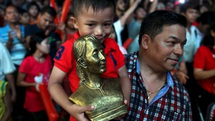 A young boy holds a bust of Aung San Suu Kyi.
