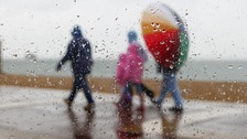 family walks along the seafront in Southsea, Hampshire in the rain