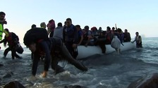 One man slips in the shallows as another boat of refugees lands on Lesbos