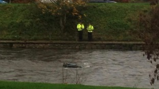 The roof of a car submerged in the River Kent