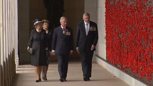 Camilla and Charles walk past a wall of poppies in Canberra.