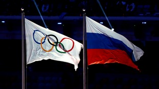 The Olympic rings fly alongside the Russian flag