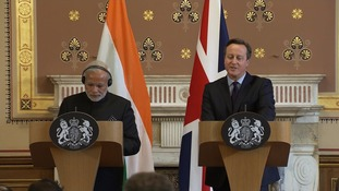 David Cameron speaks at a press conference alongside India's prime minister.