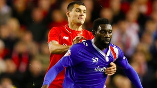 Jabo Ibehre battles Liverpool's Dejan Lovren for the ball.