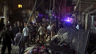 Residents inspect the aftermath of two explosions in Beirut's southern suburb, a stronghold of Lebanese Hezbollah.