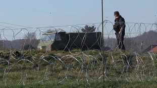 A soldier guards the razor wire fence along Slovenia's border.
