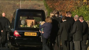 Family gather behind the hearse.