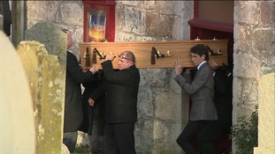 The pallbearers carry the coffin.