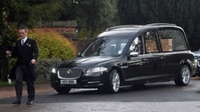 The funeral car arrives at the church.