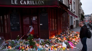 A man stand in front of flowers and candles on display in front of the Café Carillon in the Rue Alibert in Paris, France,