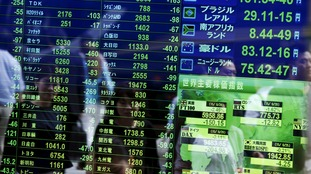 Passersby are reflected on a screen displaying stock quotation, the stock market indices