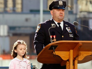 New York police officer James Smith reads the names of victims during a ceremony to mark the fifth anniversary of the September 11 attacks at the site of the World Trade Center as his daughter Patricia stands by him, in New York September 11, 2006