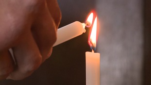 A candle is lit at Derby Cathedral to remember the dead.