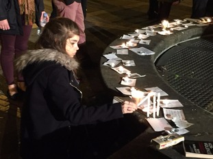 One student lighting a candle at the tribute around a fountain on the University of Birmingham campus.