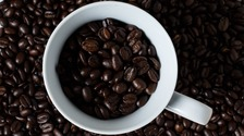 A mug surrounded by coffee beans