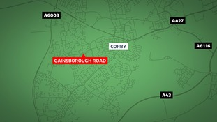 An elderly woman was robbed while waiting for a bus in Corby.