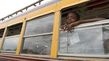 A child looks out of a bus window as residents of a camp for displaced people of the 2010 earthquake evacuate