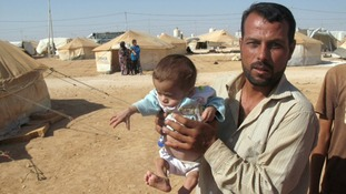 Bashar, a refugee from the city of Aleppo, presents his nine-weeks-old son Ahmed at the refugee camp Saatari, Jordan