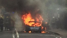 Firefighters extinguish a Vauxhall Zafira which caught light near a level crossing in south west London.