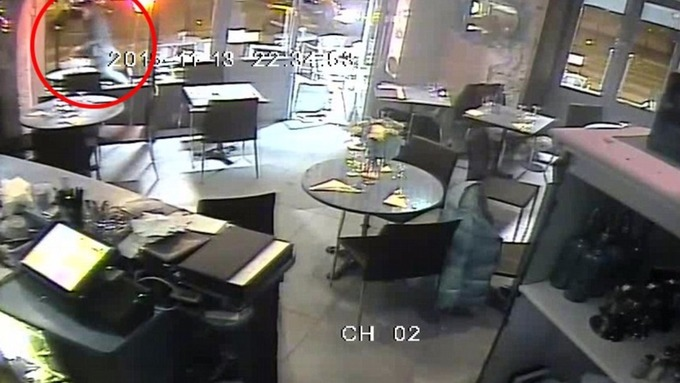 The gunman is seen running outside the restaurant as a vehicle approaches outside.