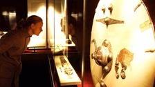 A visitor looks at an exhibition of artefacts from Sutton Hoo.